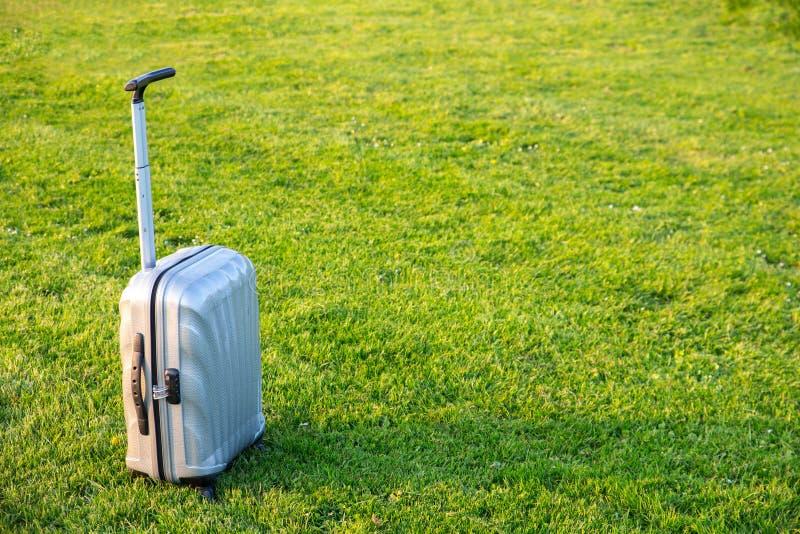 Mala de viagem de prata na grama verde fotografia de stock