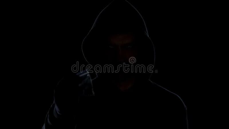 Mala hierba de ofrecimiento masculina de la marijuana del traficante en bolso de la muestra en el fondo oscuro, crimen fotos de archivo