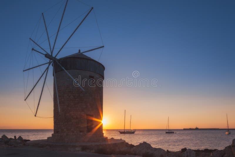 Mala på bakgrunden av resningsolen i hamnen av Mandraki Rhodes ö Grekland royaltyfri bild