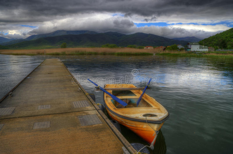Mala Prespa lake and the pier of Mikrolimni village. A beautiful spring picture of the Mala Prespa lake in Greece. Here I caught reflections of clouds, alone royalty free stock photos
