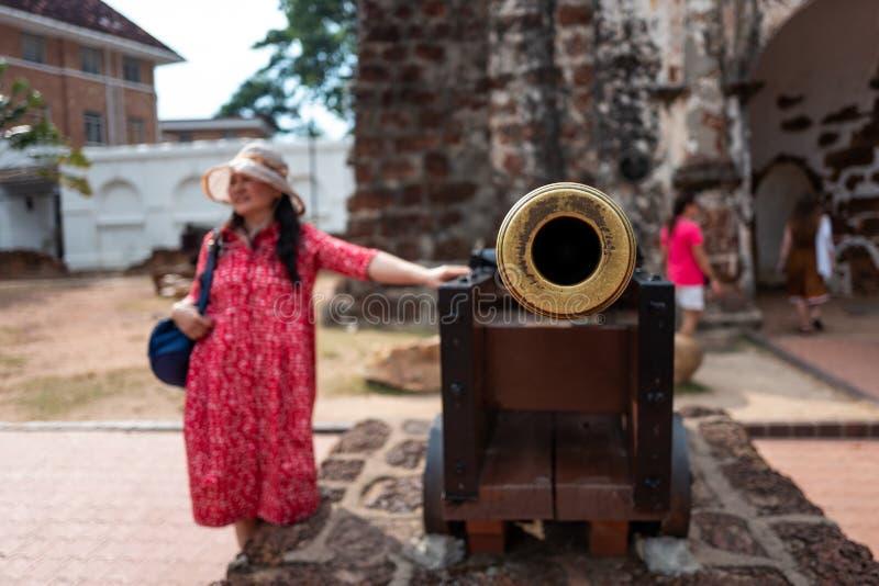 Malaca, Malasia - 28 de febrero de 2019: El turista asiático pone su mano en viejo canon en la ciudad vieja de Malaca imagenes de archivo