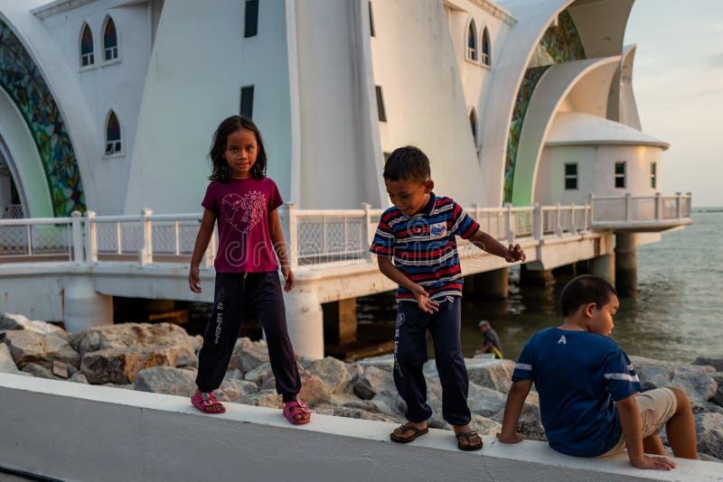Malaca, Malasia - 28 de febrero de 2019: los niños juegan en el fron de la mezquita de los estrechos de Malaca conocida como Masj fotos de archivo libres de regalías