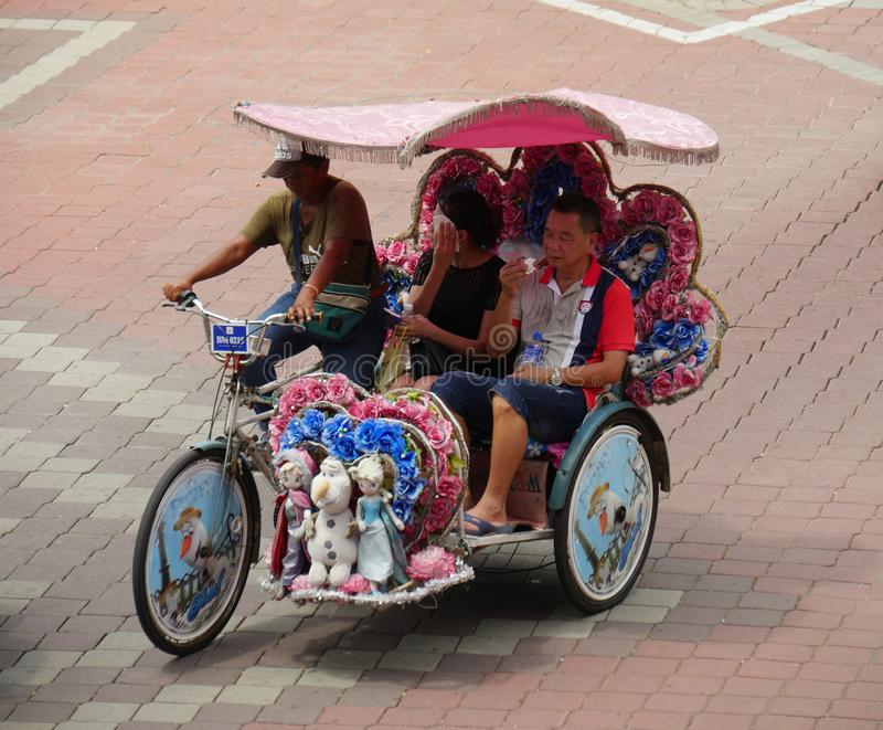 Malacca, Malaysia--February 2018: A couple of tourists ride a colorful trishaw along the brick-paved Dutch Square in Melaka, royalty free stock photos