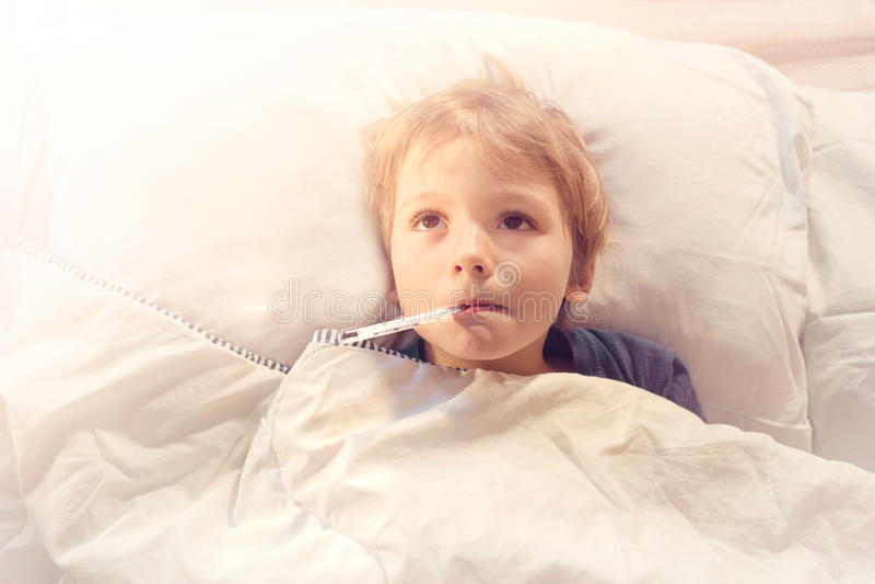 Malade d'enfant dans le lit avec la fièvre et le thermomètre photo libre de droits
