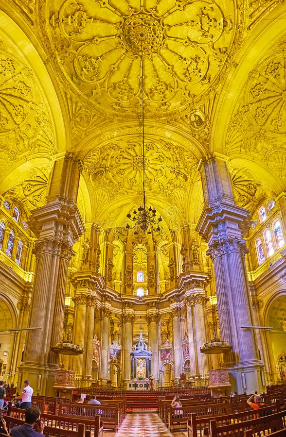 In Malaga Cathedral, Spain. MALAGA, SPAIN - SEPTEMBER 26, 2019: The main altar of Cathedral, surrounded by carved columns, painted icons and stained-glass royalty free stock image