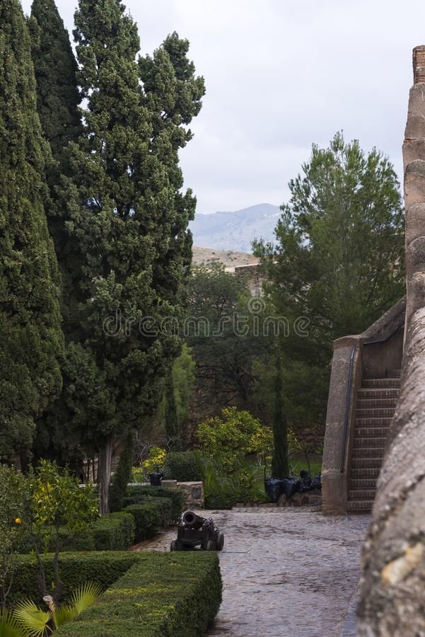 Malaga, Espagne, février 2019 Le vieil escalier, la cour intérieure avec le vieux canon et les murs en pierre antiques de l'Arabe photos libres de droits