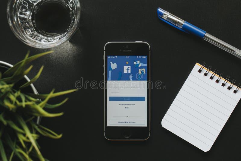 MALAGA, ESPAGNE - 6 MARS 2018 : Vue supérieure de téléphone portable avec Facebook APP dans l'écran, sur un bureau noir près de s photo libre de droits