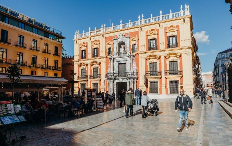 MALAGA, ESPANHA - 5 de dezembro de 2017: Fachada episcopal e turista do palácio que sentam-se nos terraços dos restaurantes e que imagens de stock