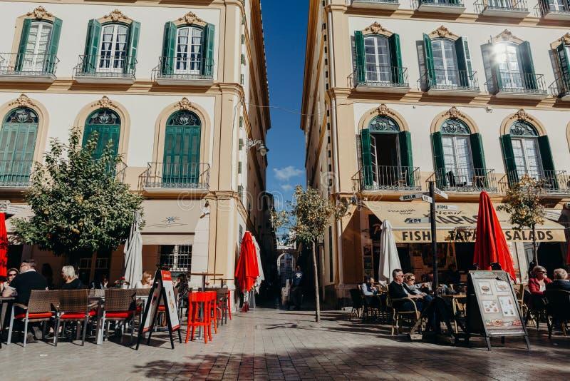 MALAGA, ESPANHA - 5 de dezembro de 2017: Os turistas que sentam-se em um terraço barram ter uma bebida no quadrado popular de Mer imagem de stock royalty free