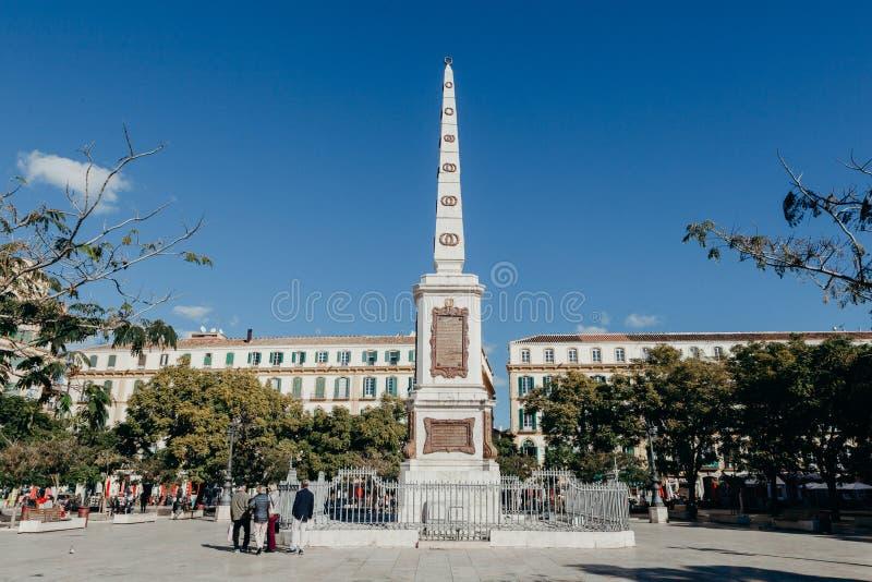 MALAGA, ESPANHA - 5 de dezembro de 2017: Quadrado e monólito no centro, e povos de Merced que andam em torno dele, o 5 de dezembr foto de stock