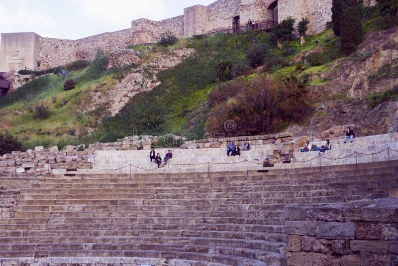 Malaga, Espanha, em fevereiro de 2019 Teatro romano no fundo do Alcazaba Os povos relaxam nos bancos de pedra para espectadores e foto de stock royalty free