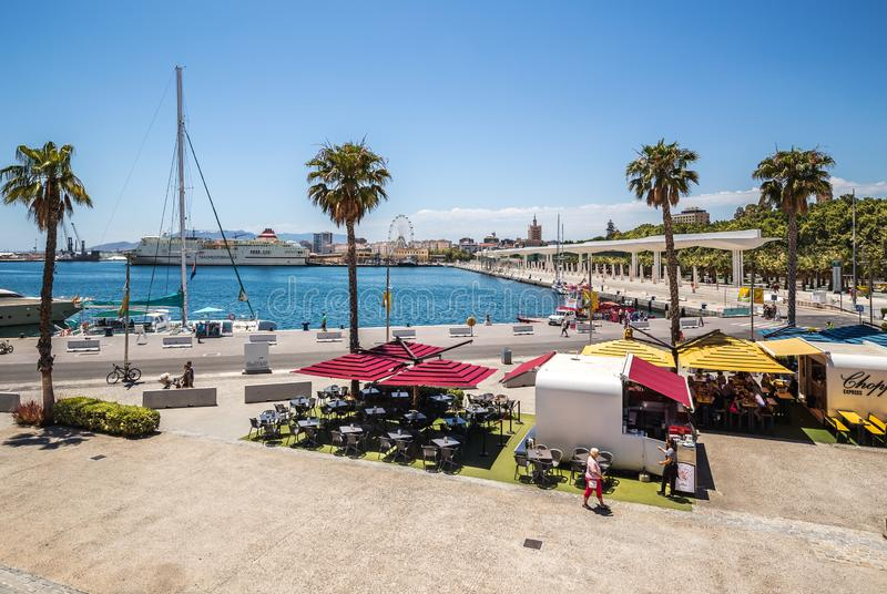 Malaga seaport, Spain. Malaga, Spain - June 20, 2018: Promenade of Malaga with a view of the pedestrian area, the port, the Ferris wheel and cafe stock image