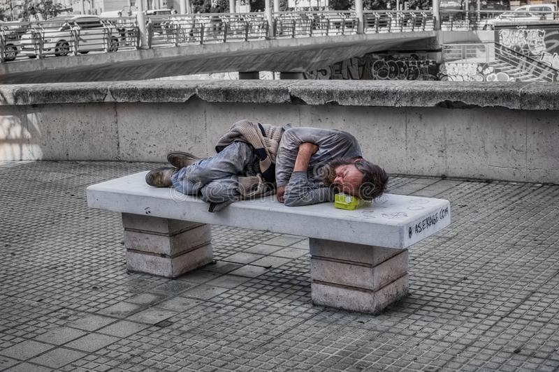 Homeless man sleeps on the stone bench in downtown stock photography