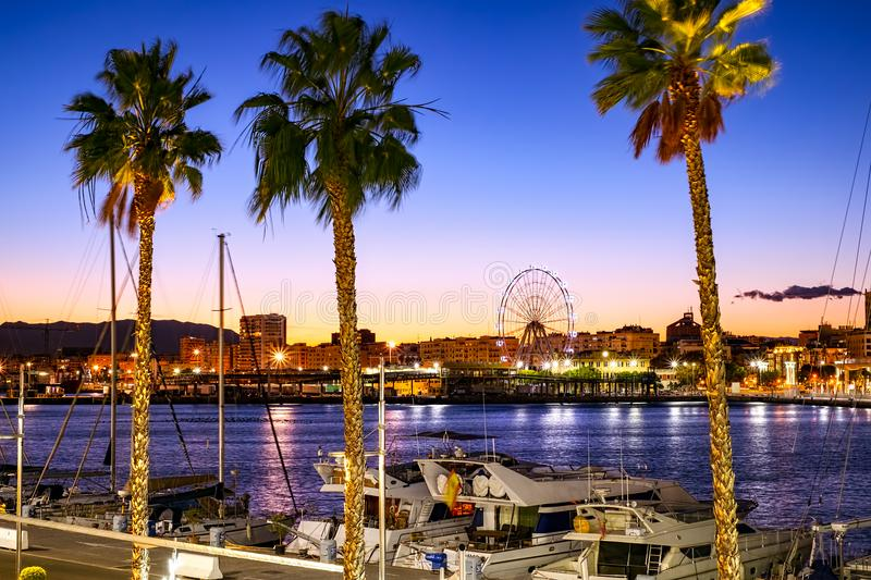 Malaga port and Ferris wheel. Malaga, Spain - December 1, 2017. Luxury Boats in Malaga port and Ferris wheel in the background stock images