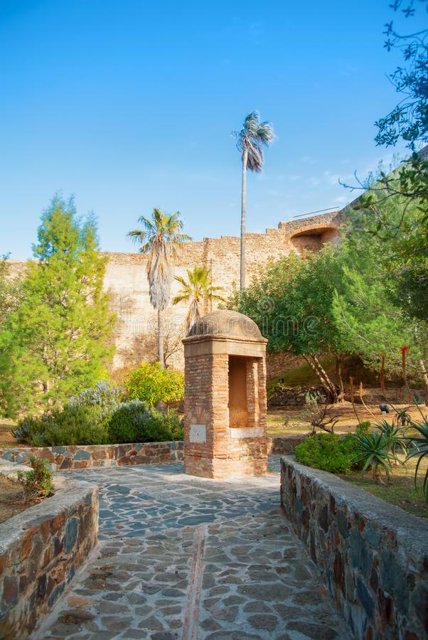 MALAGA, SPAIN - FEBRUARY 16, 2014: A view to old medieval walls, trees, plants, palms and a tower at Gibralfaro Castle royalty free stock images