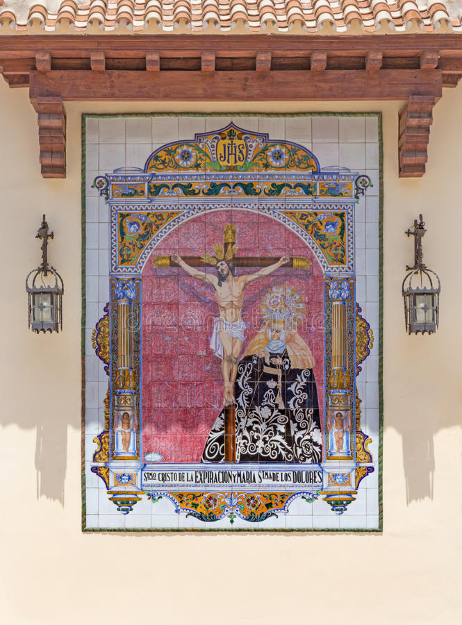 MALAGA, SPAIN - MAY 25, 2015: The ceramic tiled, cried Madonna under the Crucifixion on the facade of church Parroquia de San Pedr. O St. Peters church by royalty free stock photo