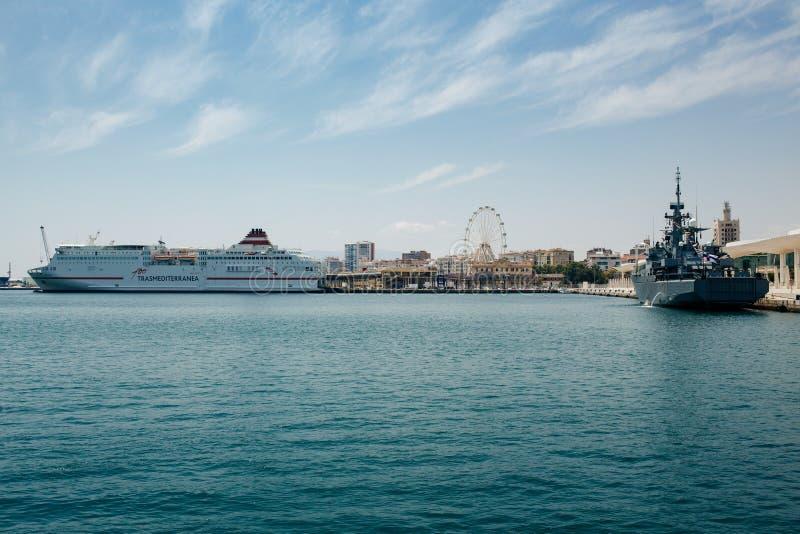Port of Malaga. MALAGA, SPAIN - MAY 19, 2018: Port of Malaga with ferryboat Trasmediterranea, finnish warship and Ferris wheel in background stock photography