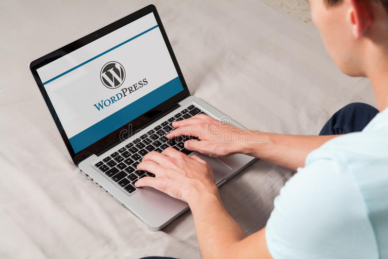 MALAGA, SPAIN - NOVEMBER 10, 2015: Wordpress brand logo on computer screen. Man typing on the keyboard. Man using Wordpress CMS to design a website. WordPress