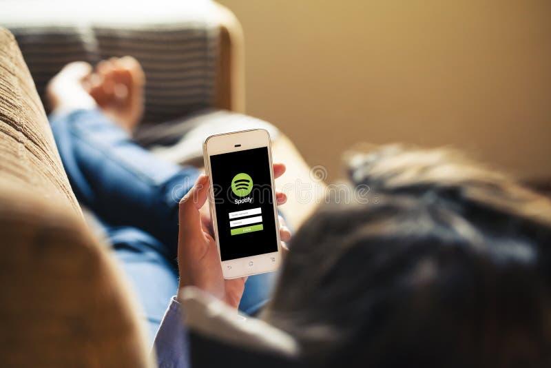 MALAGA SPANIEN - APRIL 26, 2015: Spotify App i en mobil skärmhåll av kvinnan, medan ligga på en soffa hemma royaltyfri fotografi