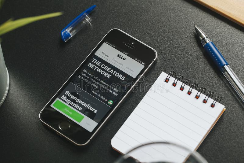 MALAGA SPANIEN - MARS 6, 2018: Mobiltelefon med Ello app i skärmen som förläggas på ett svart skrivbord med kontorsmaterial royaltyfria foton