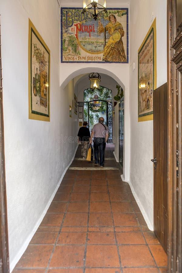 MALAGA SPANIEN - September 2nd, 2018: Höga par som går över korridoren av den populära restaurangen El Pimpi, det mest berömd royaltyfria foton