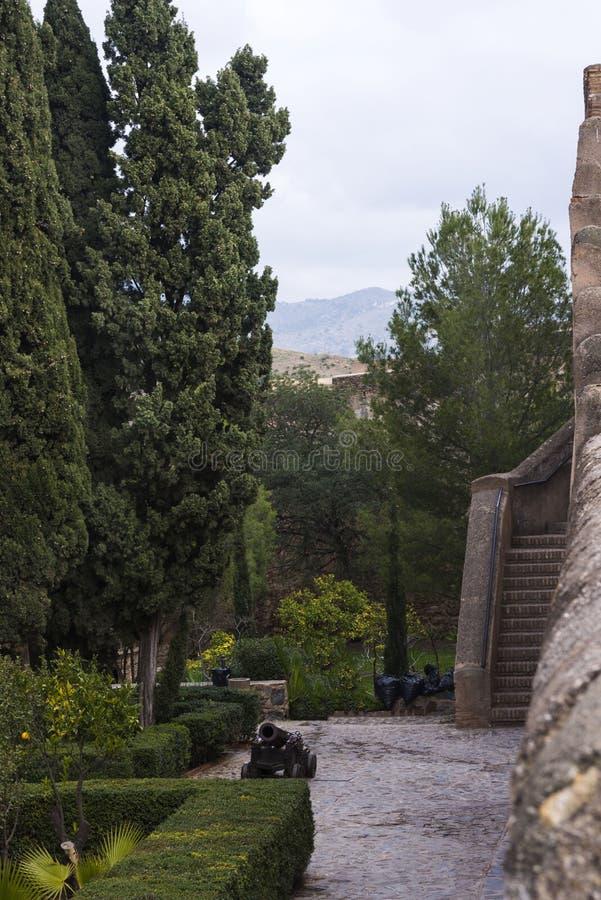 Malaga, Spanje, Februari 2019 De oude trap, de binnenbinnenplaats met het oude kanon en de oude steenmuren van Arabisch F royalty-vrije stock foto's