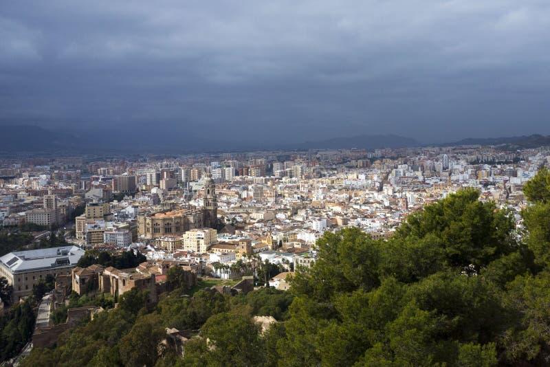 Malaga, Spanje, Februari 2019 Panorama van de Spaanse stad van Malaga Gebouwen tegen een bewolkte hemel Dramatische hemel over de royalty-vrije stock foto