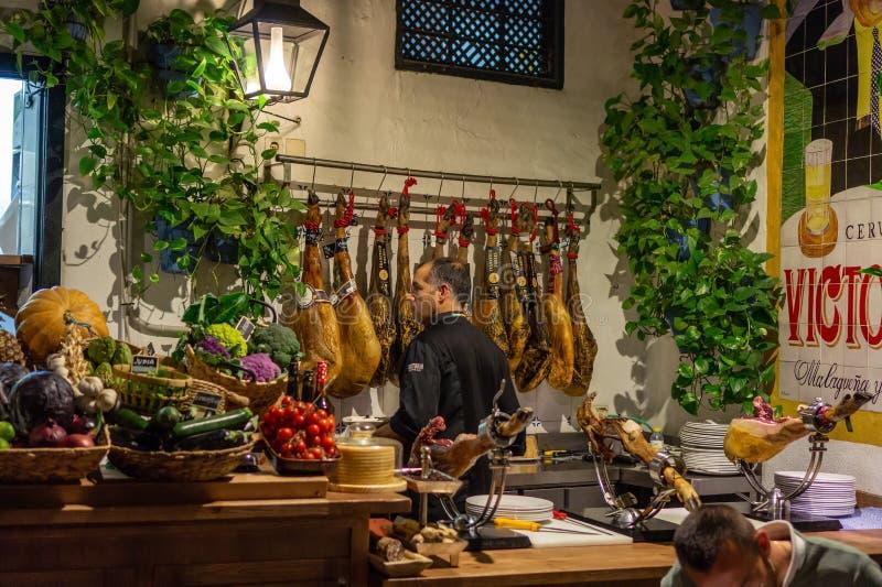 Malaga, Spanje 04 04 2019: mensenkelner in pimpirestaurant van Gr in Malaga dat plakken van traditioneel Spaanse jamon snijdt royalty-vrije stock afbeelding