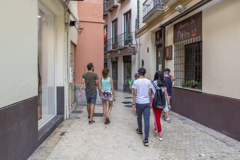 MALAGA, SPANJE - September tweede, 2018: Toeristen die over een smalle steeg tijdens een reis in het stadscentrum lopen van Malag stock foto's