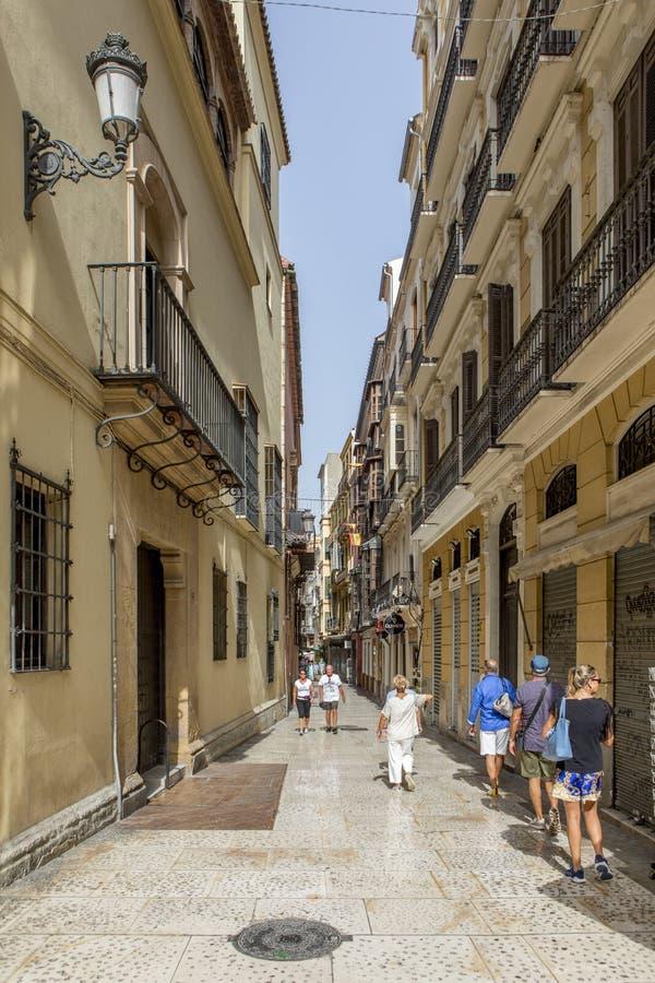 MALAGA, SPANJE - September tweede, 2018: Toeristen die over een smalle steeg tijdens een reis in het stadscentrum lopen van Malag royalty-vrije stock foto's