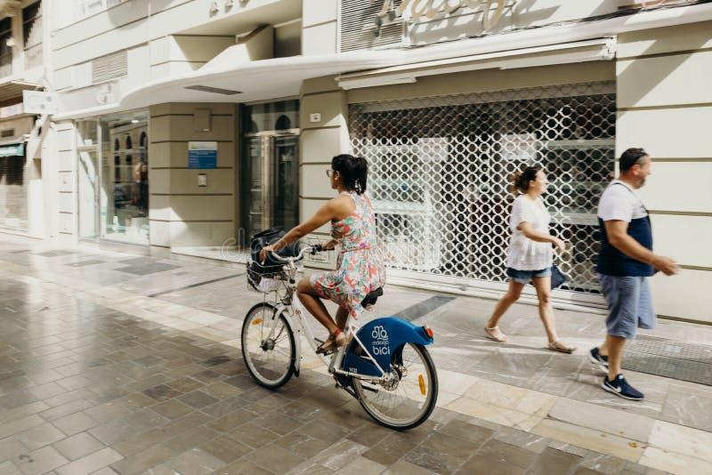 MALAGA, SPANJE - September tweede, 2018: Vrouw die een fiets berijden tijdens een reis in het stadscentrum van Malaga, Spanje stock foto
