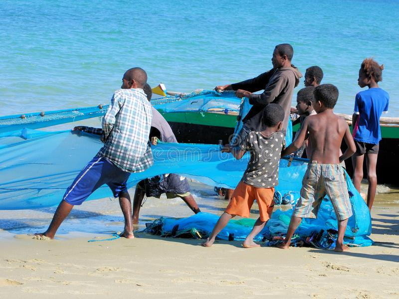 Malagasy fishermen get fishing nets from the sea royalty free stock photos