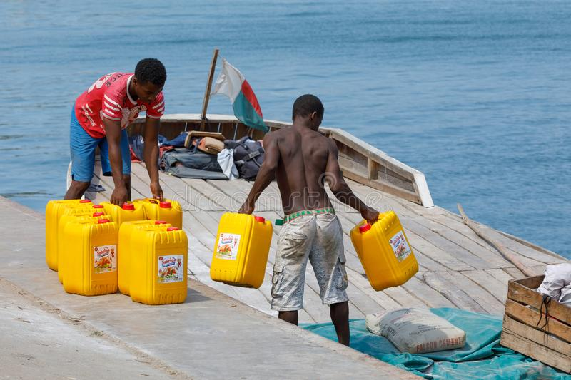 Malagasy men transport cargo from ship in port of Nosy Be, Madagascar royalty free stock images