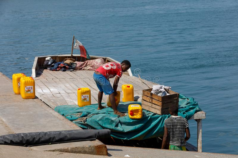 Malagasy men transport cargo from ship in port of Nosy Be, Madagascar royalty free stock image