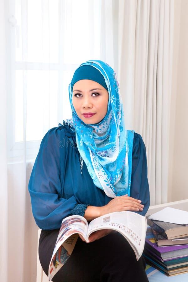 Malajiska muslimsk kvinna som tycker om en avslappnande tidläsning arkivfoton