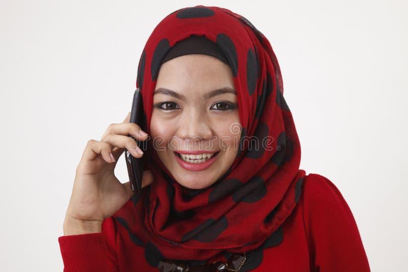 Malajska kobieta opowiada z mądrze telefonem obraz stock