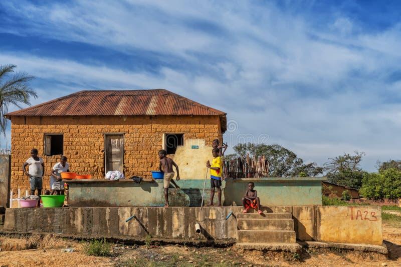 MALANJE/ANGOLA - 10. März 2018 - Afrikanerinnen und Kinder, die Kleidung an einer Wasserquelle in ländlichem Afrika, Angola wasch lizenzfreie stockfotografie