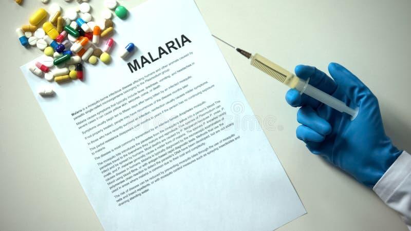 Malariawoord op document, artsenhand met spuitpillen en tabletten wordt getypt op lijst die stock afbeeldingen