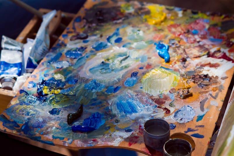 Malarz drewniana paleta zakrywająca z bałaganem świeże mieszane jaskrawe nafciane farby, kreatywnie artystyczny nieład przy lata  zdjęcia royalty free