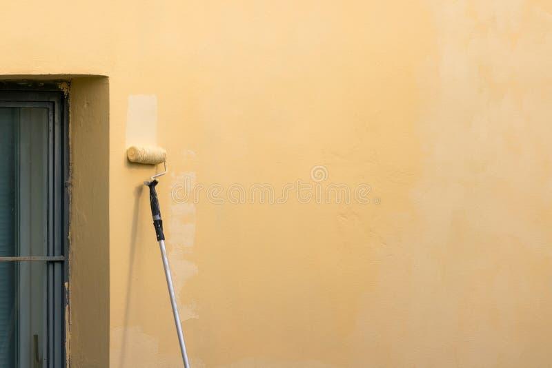 Malarz maluje budować zewnętrzną ścianę z rolownikiem Rolownik ręcznie maluje budynek z żółtą farbą z długim kijem obrazy stock