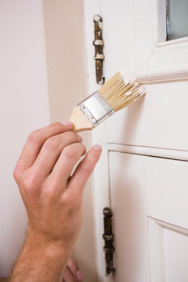 Malarz maluje drzwi biel obraz stock