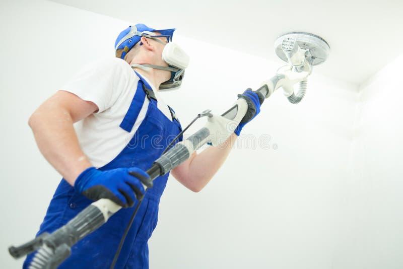 Malarz praca z sufitem polerujący powierzchnię i sanding po kitu dla malować obraz royalty free
