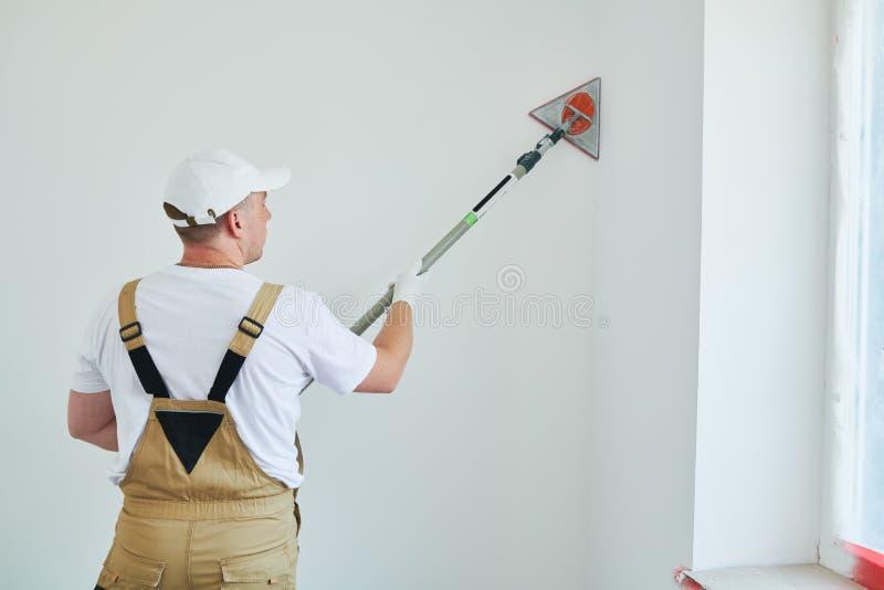 Malarz pracy kąta sander sanding ściennego kąt ukazuje się po kitu dla malować fotografia stock