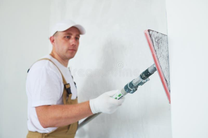 Malarz pracy kąta sander sanding ściennego kąt ukazuje się po kitu dla malować obraz royalty free