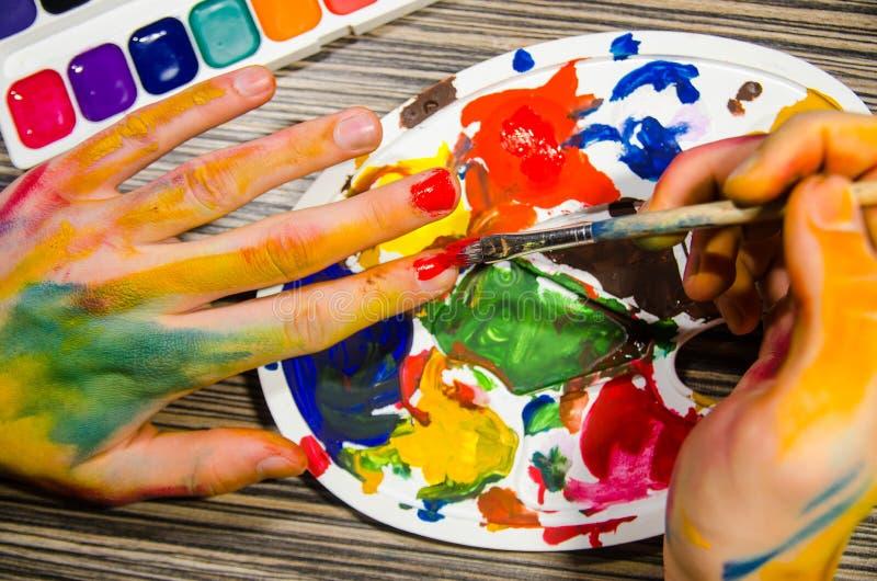 Malarz ręki robi manicure'owi z czerwonym guaszem barwią zdjęcie stock