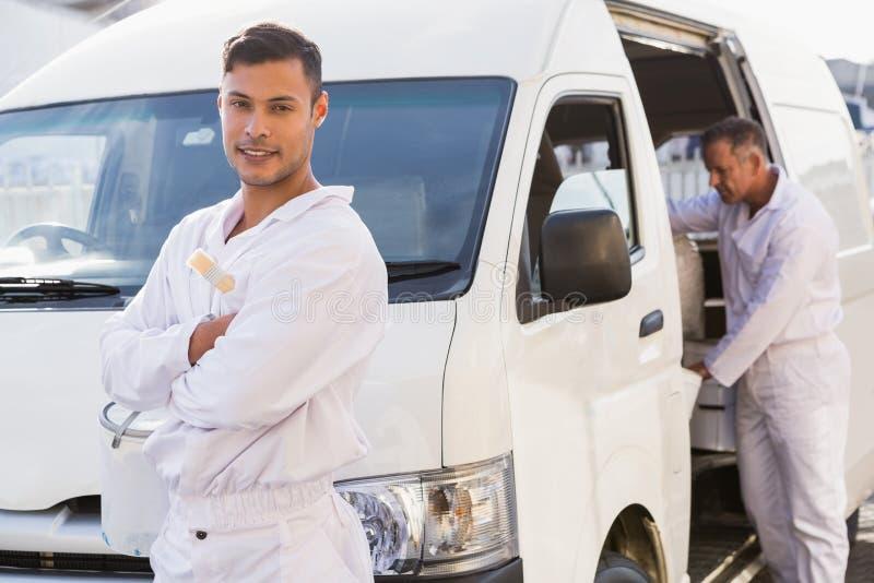 Malarz uśmiecha się opierać przeciw jego samochodowi dostawczemu zdjęcia royalty free