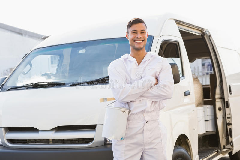 Malarz uśmiecha się opierać przeciw jego samochodowi dostawczemu zdjęcie stock