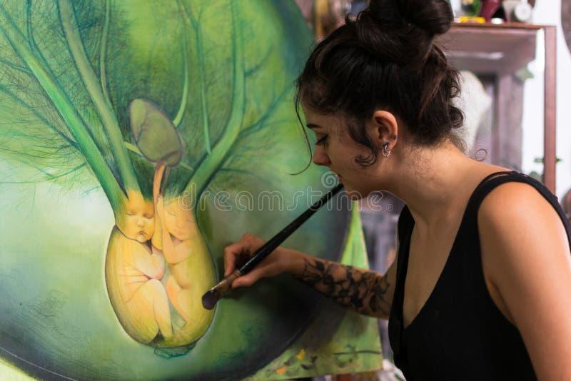 Malarz uzupełnia jej obraz w jej studiu zdjęcie royalty free