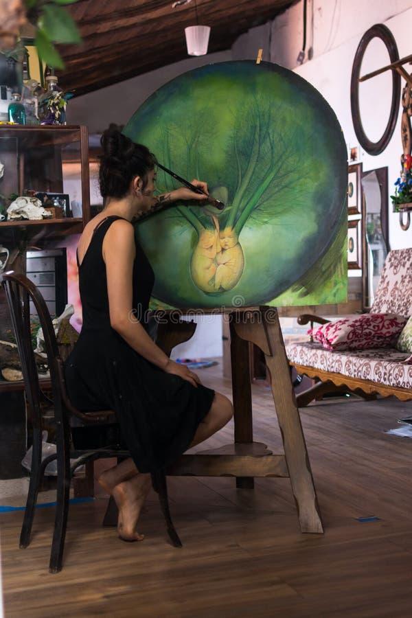 Malarz uzupełnia jej obraz w jej studiu zdjęcia stock