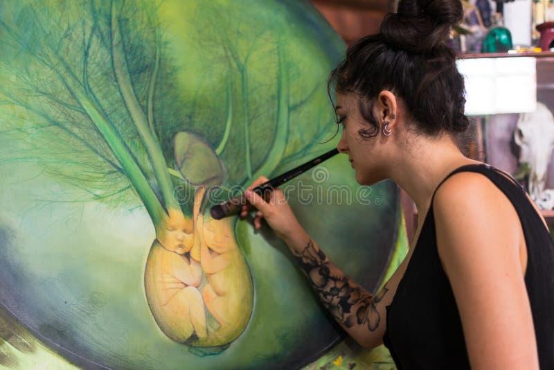 Malarz uzupełnia jej obraz w jej studiu obraz stock